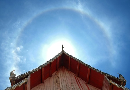 circular rainbow over church roof photo