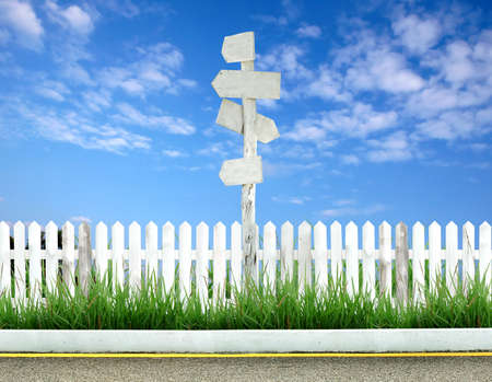 wooden signpost with white fence and blue sky Stock Photo - 9573855