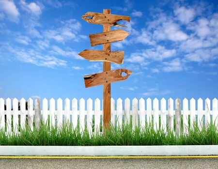 signpost: wooden signpost with white fence and blue sky