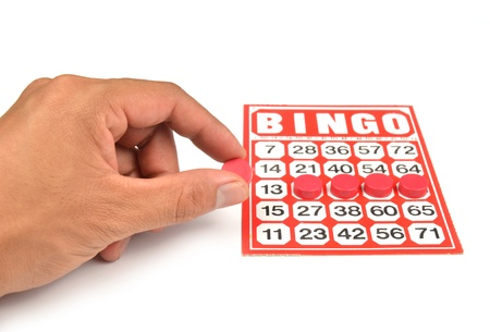 bingo card with hand hold winning chips