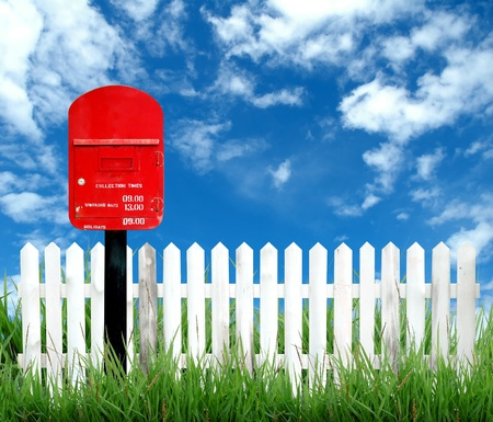red postbox with white fence and blue sky photo