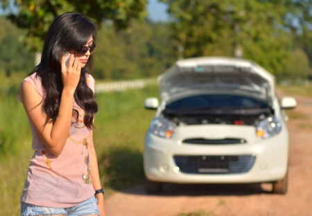 A woman calls for assistance  after her car broke down  photo