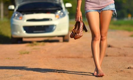 broken car: Una mujer mantenga sus zapatos y caminar despu�s de su coche se averi�