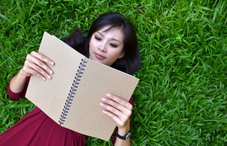 Woman lying on green grass with a book  photo