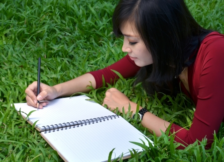 pretty women lying on green grass and writing book photo