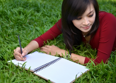describe: pretty women lying on green grass and writing book