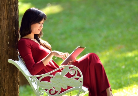 pretty woman using  tablet in the garden Stock Photo
