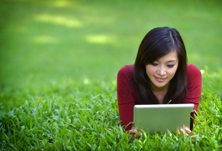 pretty woman using tablet outdoor laying on grass