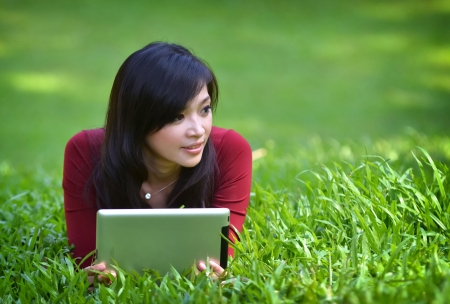 pretty woman using tablet outdoor laying on grass photo