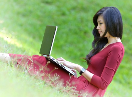 pretty  woman with laptop on green grass at the garden  photo