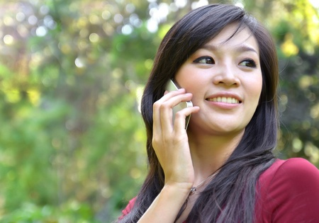 pretty woman making a phone call in the garden Stock Photo - 16141432