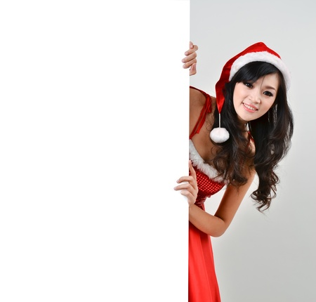 santa girl: Santa woman  holding a white poster isolated a on gray background