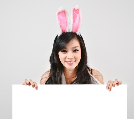 Sexy bunny girl hold white board Isolated on gray background photo