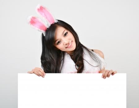 섹시한 토끼 소녀는 회색 배경에 고립 된 화이트 보드를 개최