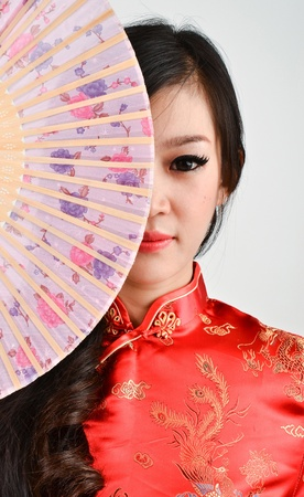 chinese dress: pretty women with Chinese traditional dress Cheongsam and hole Chinese Fan on gray background