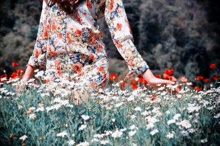women in walk and pat flower in the garden photo
