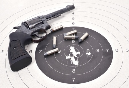 old revolver gun with bullet on the target photo
