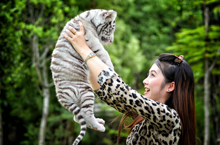 pretty women hold baby white bengal tiger photo