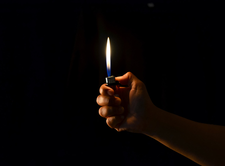 hand hold a lighter in dark background photo