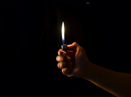 hand hold a lighter in dark background photo
