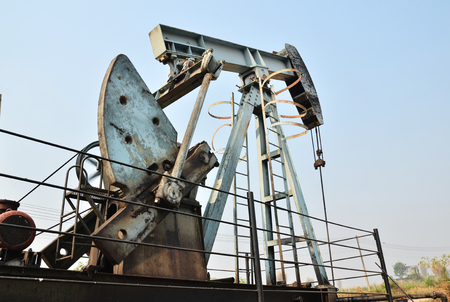 dug well: old pumpjack pumping crude oil from oil well