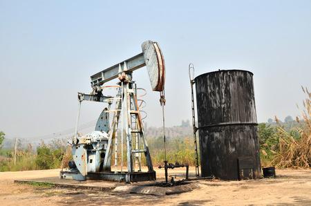 pozo petrolero: pumpjack viejo bombeo de petróleo crudo de los pozos de petróleo Foto de archivo