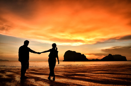 Romantic couple holding hands at sunset on the beach
