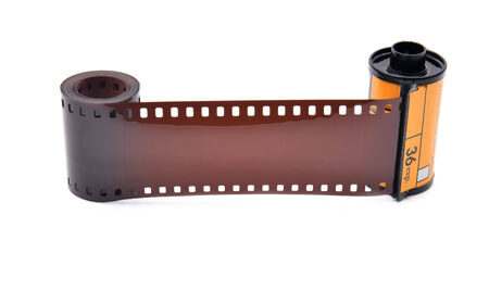 old photograph: 35 mm film cartridge on white background Stock Photo