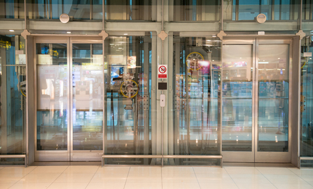 glass doors: transparent airport elevator with no people inside Editorial