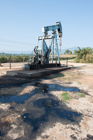 oilwell: pump jack with crude oil contaminatate to environment