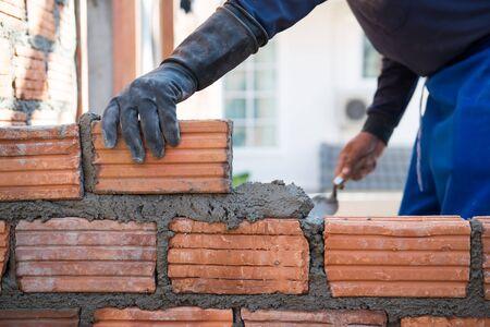 벽돌로 된 벽돌 집 벽을 지은 작업자
