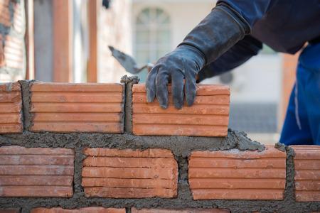 brick work: Worker building masonry house wall with bricks