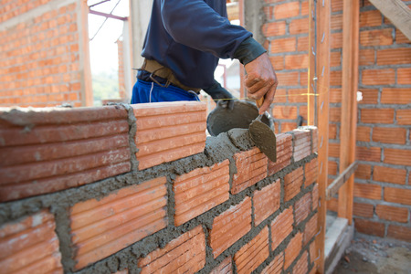 Worker building masonry house wall with bricks