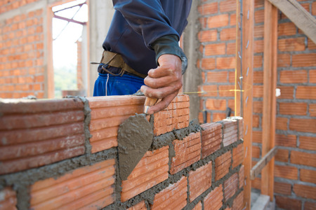 Worker building masonry house wall with bricks