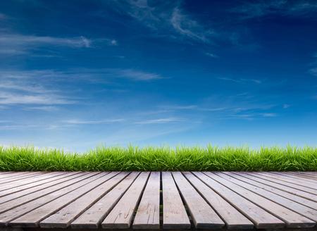 houten terras met verse lente groen gras en blauwe hemel
