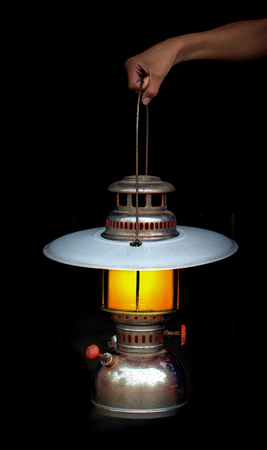 kerosene lamp: hand hold old storm lantern in the dark background