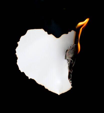 papel quemado: de papel en forma de corazón en llamas sobre fondo negro