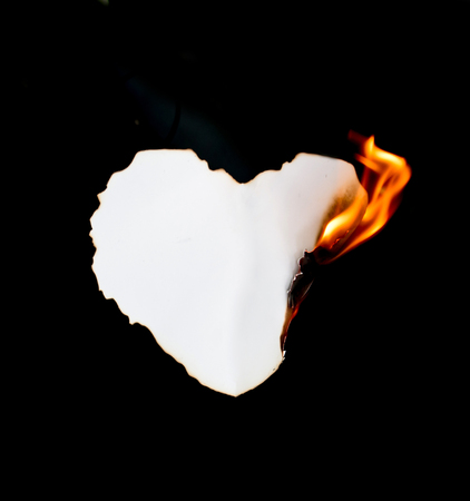 flame background: heart shape paper burning on black background