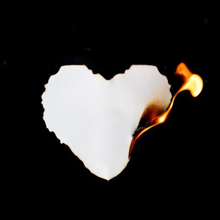 burning: heart shape paper burning on black background