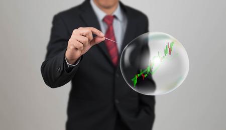 crisis economica: aguja agujero de la mano con la carta común en la burbuja