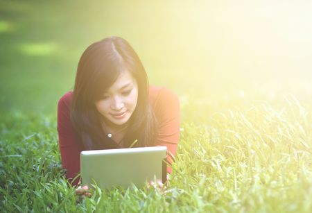 pretty woman using tablet outdoor laying on grass with flare light photo