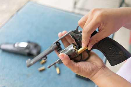 bullet proof: people load bullets into revolver gun befor shooting