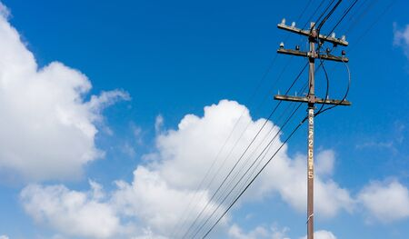electric blue: Old wooden electric pole and blue sky background