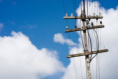 Old wooden electric pole and blue sky background