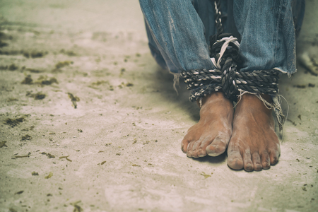 hopeless man feet tied together with rope, human trafficking