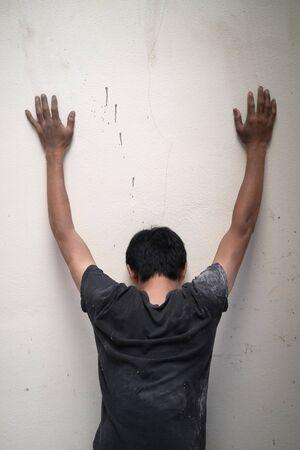 maltreatment: hopeless man show hands up facing the wall