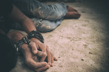 human trafficking: hopeless man hands tied together with rope, human trafficking