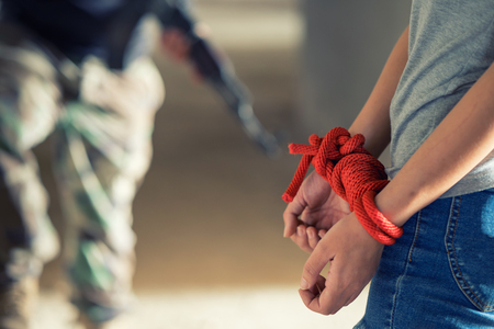 Tied rope hands of abused woman, human trafficking. Stock Photo
