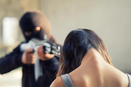 誘拐された女性を銃で脅して目出し帽の男 写真素材