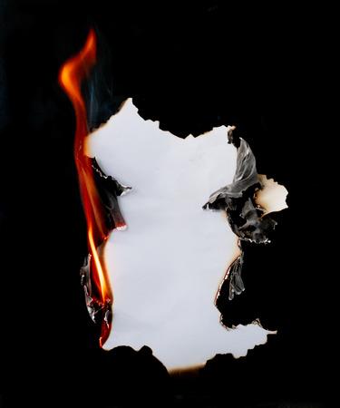 brennendes Stück Papier auf schwarzem Hintergrund